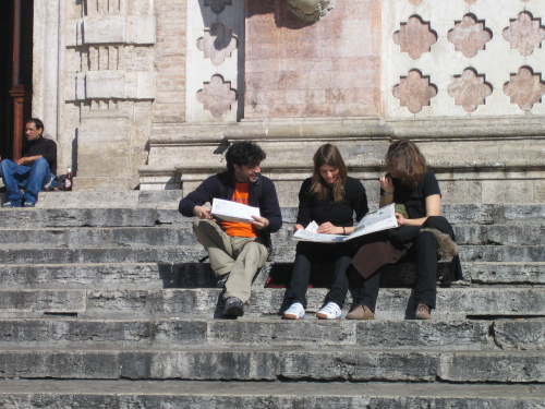 three people sitting on stairs comparing data collected during an OpenStreetMap field survey